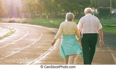Senior couple walking along the running track - Senior...