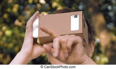 Exploring virtual reality in cardboard VR glasses - Woman...
