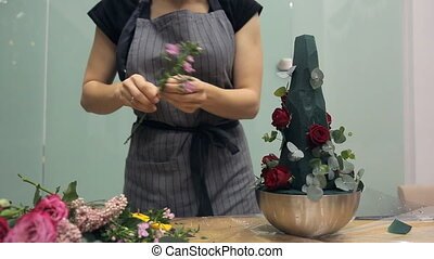 Florist brings floral bouquet of flowers for floristic composition
