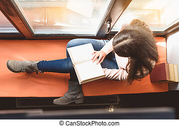 Best place for reading books - Top view of girl sitting on...