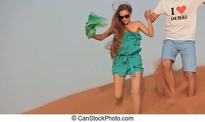 Love couple runs on the dunes of the desert 3 - Shot with a...