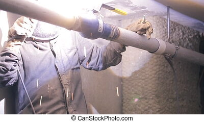 Welder uses instruments to install pipe with tap inside new...