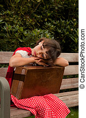 Lonely girl in red sitting on a bench with her suitcase