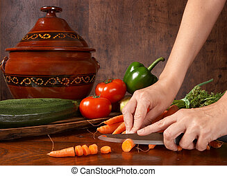 Vegetable slicing - Hands of a woman slicing vegetables on a...