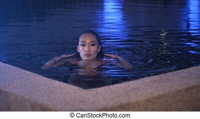 Sexy woman in bikini at the swimming pool in evening time -...