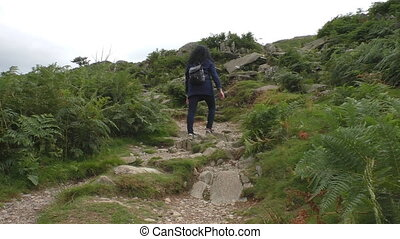 Woman climbing mountain trail
