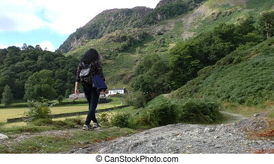Woman in countryside - Long dark haired woman with backpack...