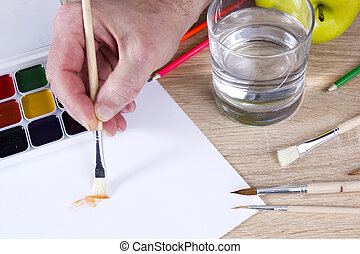 Artist's hand at work, paints, brushes and pencils - The...