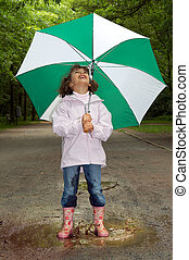 Umbrella and boots - Little girl playing in a water puddle...