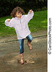 Dancing in the mud - Little girl dancing in a water puddle...