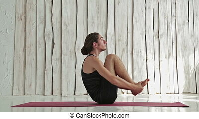 Young sporty man practicing yoga in fitness studio. White...