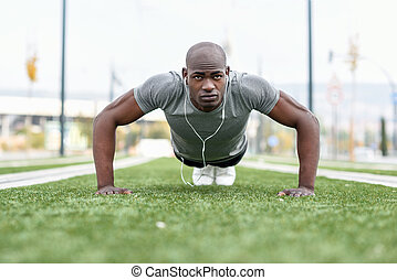 Fitness black man exercising push ups in urban background -...