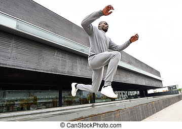 Attractive black man running in urban background - Black man...
