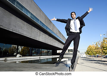 Businessman wearing blue suit and tie jumping in urban...