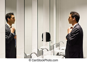 Man getting dressed in a public restroom with mirror....