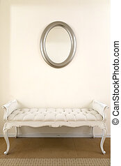 Couch with mirror - A white couch underneath a simple...