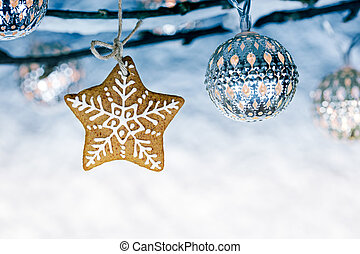 gingerbread christmas star with holiday lights hanging on bare branches