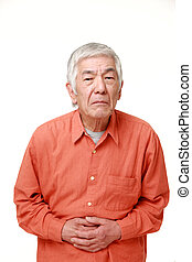 senior Japanese man suffers from stomachache - studio shot...