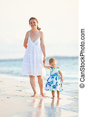 Mother and daughter on tropical beach at sunset
