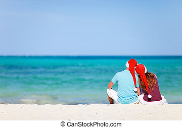 Romantic couple in Santa hats sitting on tropical beach -...