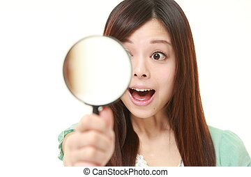 Japanese woman with a magnifying glass discover something