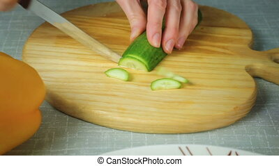 Girl with a knife cuts geen cucumber - The girl with a knife...