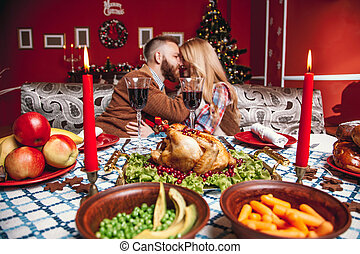 Beautiful couple kissing and holding glass of wine in a...