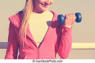 Woman doing sports outdoors with dumbbells