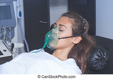 young woman with oxygen mask at hospital or cosmetics salon