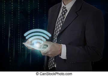Businessman hand touch screen wifi symbol on a tablet, communication concept.