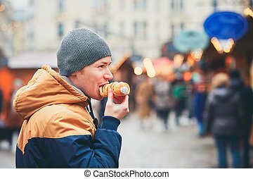 Christmas market in Vienna - Young man eating puff roll with...
