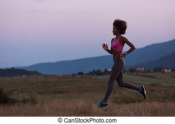 Young African american woman jogging in nature - young...