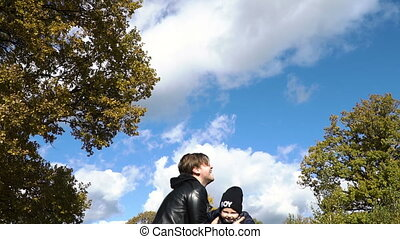 Young family in the park. - Father throws his little son...