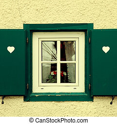 traditional bavarian small window with green shutters -...