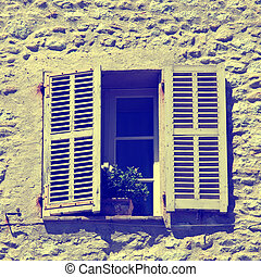 rustic window with old wood shutters in stone rural house,...