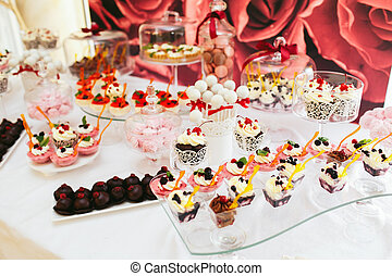 Little tasty desserts stand under glass cover