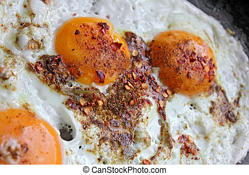 Fried eggs in with red hot chilly peppers
