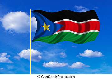 Flag of South Sudan waving on blue sky background - South...