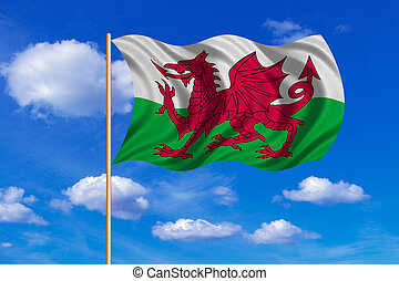 Flag of Wales waving on blue sky background - Welsh national...