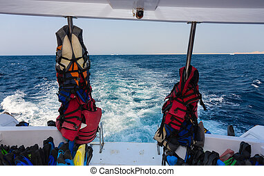 Lifejackets and other equipment for diving on back teak deck...