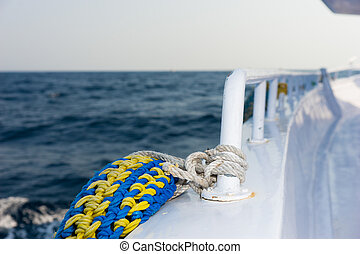 Lifebuoy tethered to the railing of the deck of cruise ship,...