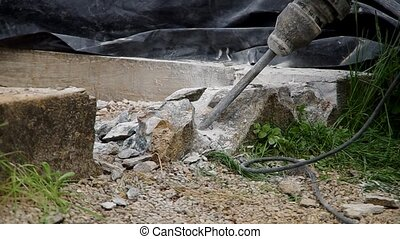 Working with jackhammer - Worker removes old concrete with...