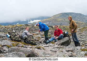 Group of travelers in mountains with knapsacks are resting