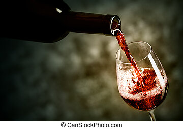 Red wine is being poured into the glass shot against dark...