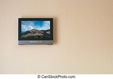Liquid-crystal television receiver on wall. Picture on...