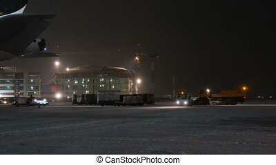 Workers and service cars work near aircraft at the airport....