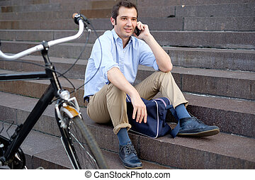 Man is resting next to his bike and using mobile phone