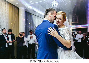 Bride's hand lies on groom's shoulder while they dance in...