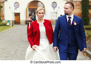 Happy bride and groom walk out of the church