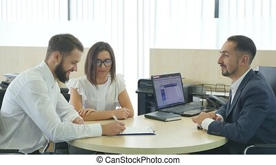 Car Dealer signing a contract to purchase and giving the key to a new car to a young attractive owners